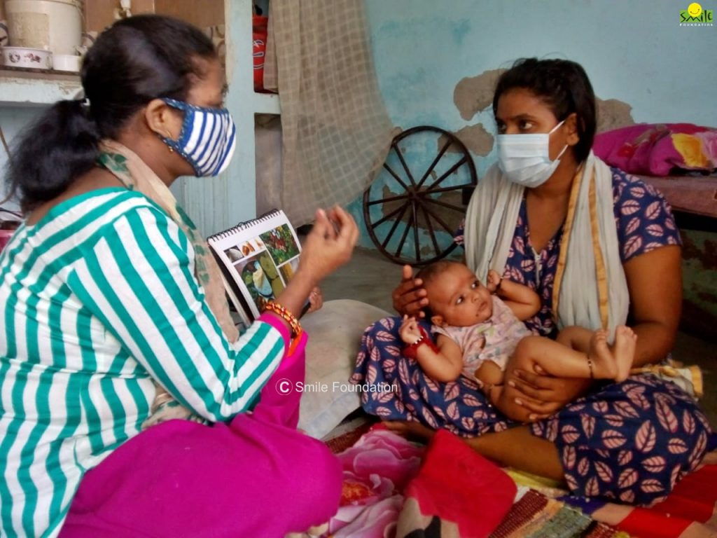 A Swabhiman volunteer helping a new mother understand the precatuions to be taken to care for her child